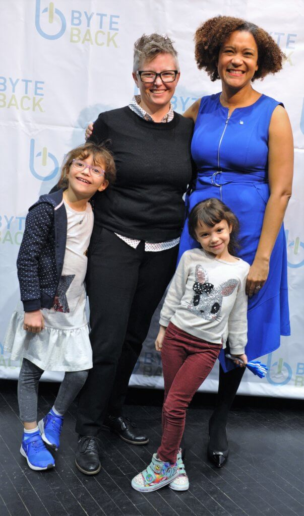 A family of two women standing with two small children in front of them