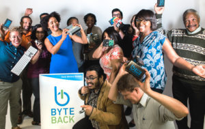 Group of about a dozen people hold up tech devices and smile