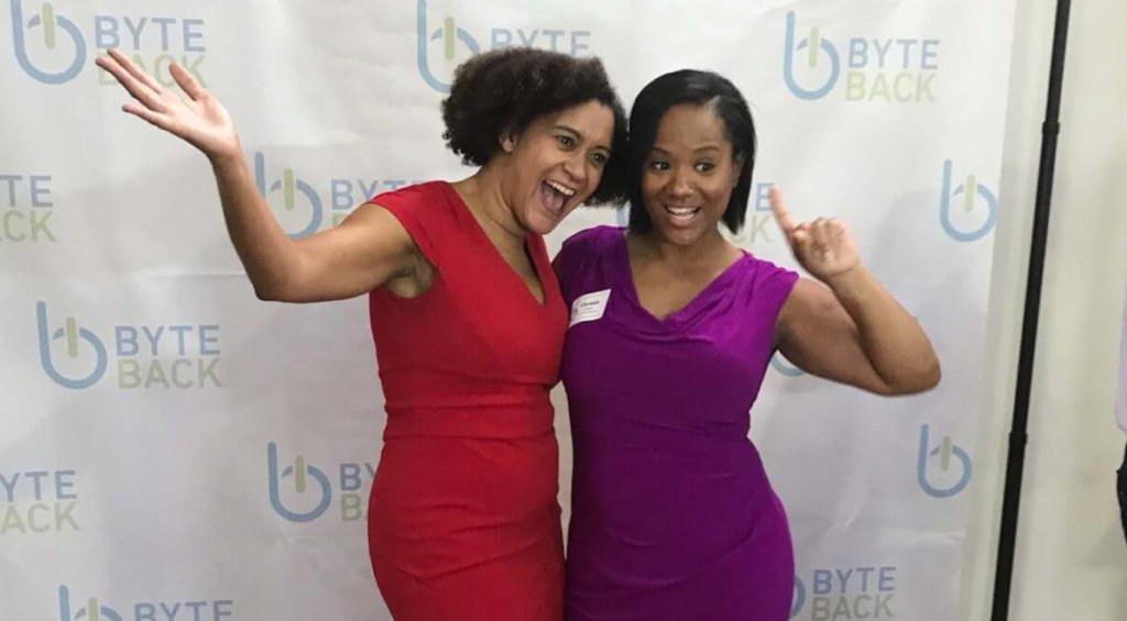 Two women pose smiling in front of a Byte Back logo backdrop